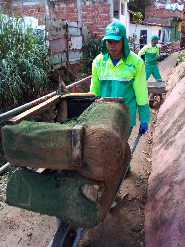 Agente de limpeza retira sofá velho de córrego. Foto: Ascom Sudes